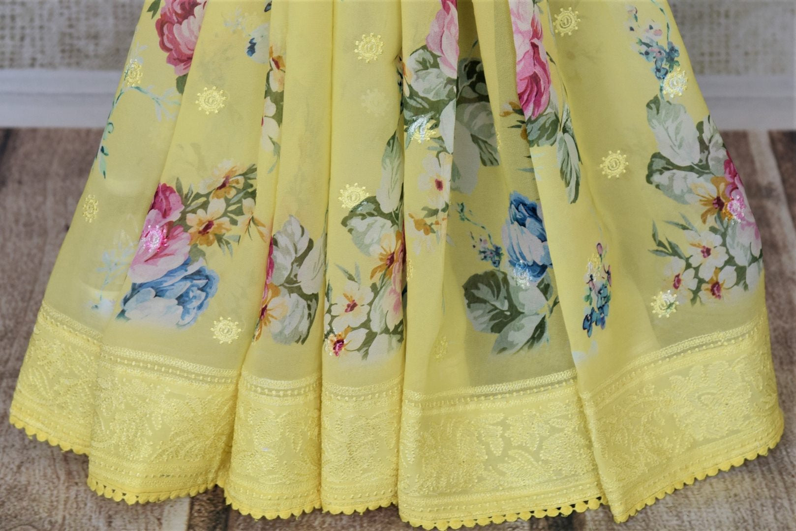 Buy beautiful lemon yellow floral georgette saree online in USA with embroidered border. Be the talk of the occasions in exquisite linen sarees, embroidered saris from Pure Elegance Indian fashion store in USA. -pleats