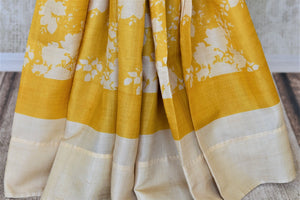 Shop yellow tassar saree online in USA with white floral print. Be the talk of the occasions in exquisite tassar sarees, handwoven silk saris from Pure Elegance Indian fashion store in USA. -pleats