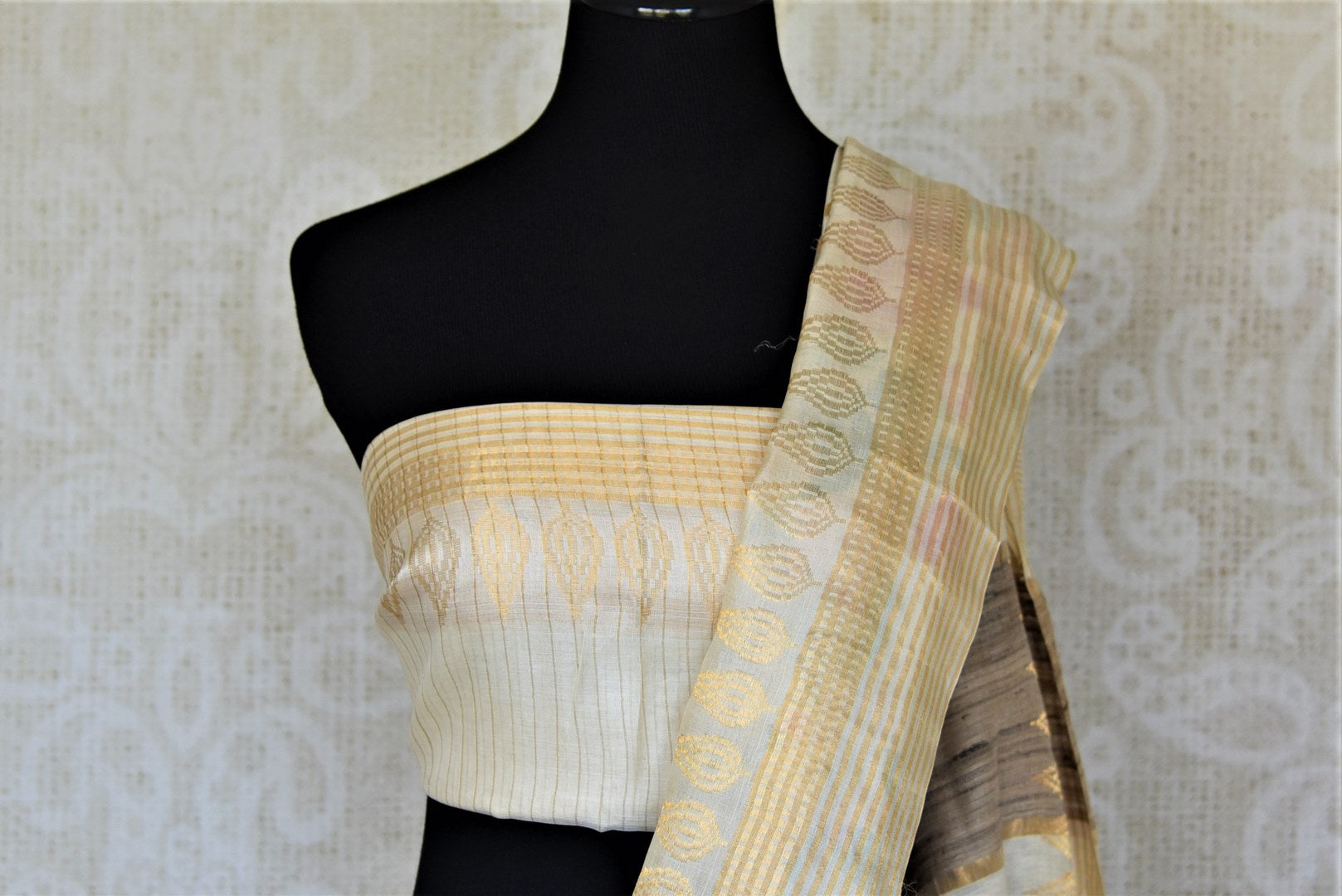 Shop charming off-white tassar sari online in USA with pink floral print. Be the talk of the occasions in exquisite tassar sarees, handwoven silk saris from Pure Elegance Indian fashion store in USA. -blouse pallu