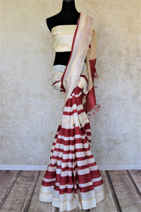 Shop elegant off-white and red stripes tassar silk saree online in USA. Be the talk of the occasions in exquisite tassar sarees, handwoven silk saris from Pure Elegance Indian fashion store in USA. -full view