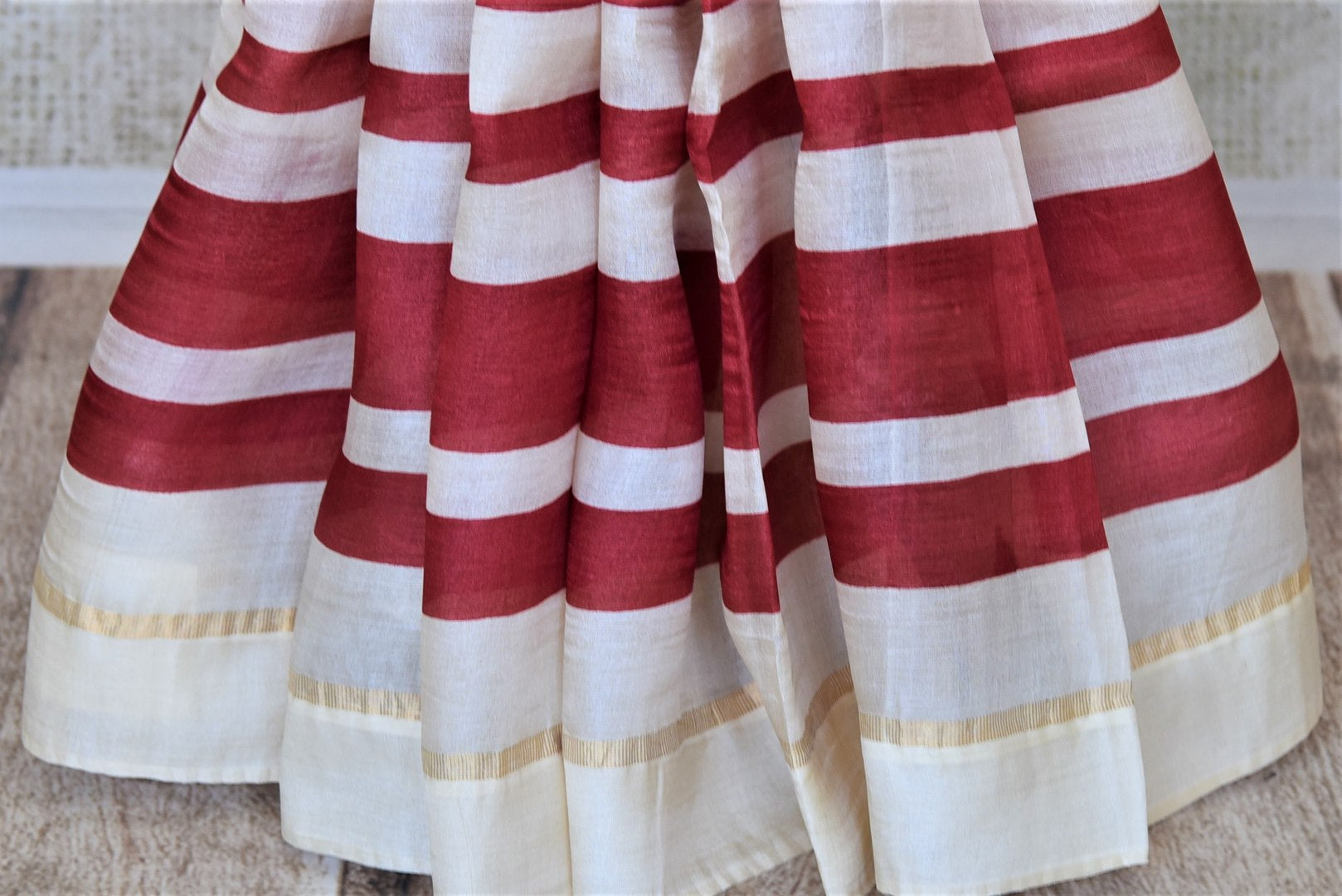 Shop elegant off-white and red stripes tassar silk saree online in USA. Be the talk of the occasions in exquisite tassar sarees, handwoven silk saris from Pure Elegance Indian fashion store in USA. -pleats