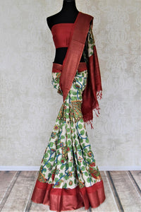 Buy elegant off-white peacock and floral print tussar silk saree online in USA with red border. Make a beautiful appearance on special occasions with exquisite Indian designer sarees, pure silk saris from Pure Elegance Indian fashion store in USA.-full view