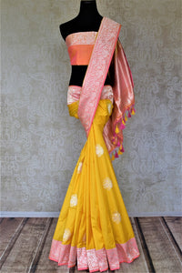 Buy charming yellow Banarasi silk saree online in USA with silver zari work on pink border. For Indian women in USA, Pure Elegance Indian fashion store brings an exquisite collection Banarasi sarees, Banarasi silk sarees, tussar sarees, zari work sarees, pure silk sarees all under one roof. Shop online now.-full view