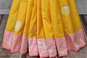 Buy charming yellow Banarasi silk saree online in USA with silver zari work on pink border. For Indian women in USA, Pure Elegance Indian fashion store brings an exquisite collection Banarasi sarees, Banarasi silk sarees, tussar sarees, zari work sarees, pure silk sarees all under one roof. Shop online now.-pleats