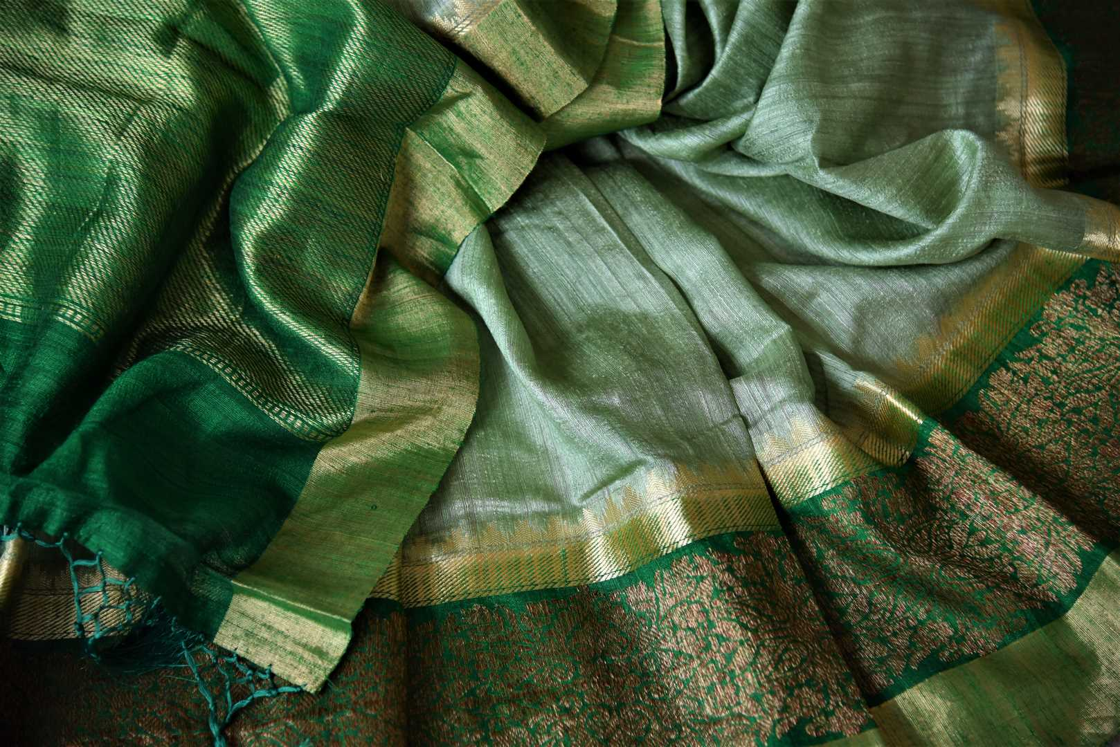 Shop dark green tussar Banarsi saree online in USA with green zari border. Choose tasteful handloom sarees for special occasions from Pure Elegance. Our exclusive Indian fashion store has a myriad of exquisite pure silk saris, tussar sarees, Banarasi sarees for Indian women in USA.-details