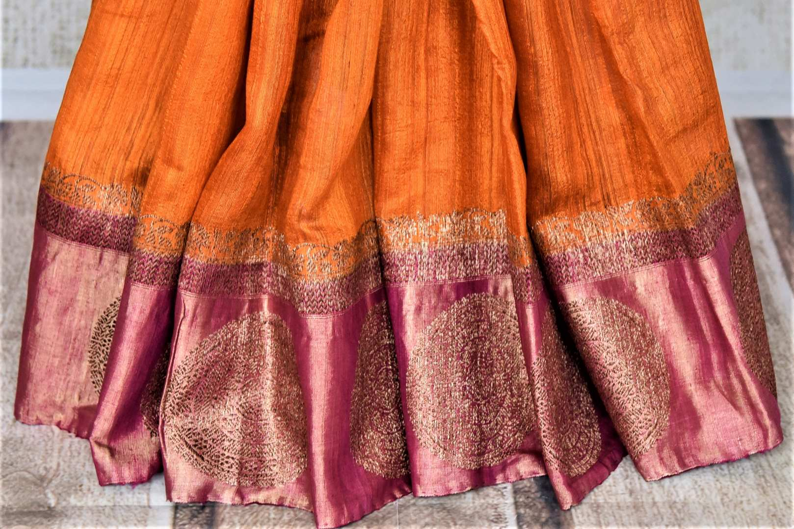 Buy beautiful orange tussar Banarsi sari online in USA with pink zari buta border. Choose tasteful handloom sarees for special occasions from Pure Elegance. Our exclusive Indian fashion store has a myriad of exquisite pure silk saris, tussar sarees, Banarasi sarees for Indian women in USA.-pleats