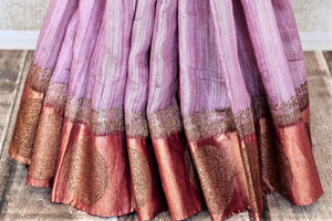 Buy beautiful lavender color tussar Banarasi saree online in USA with golden zari buta border. Be the center of attraction at weddings and parties with beautiful silk sarees, tussar sarees, embroidered sarees, partywear sarees, fancy sarees from Pure Elegance Indian fashion store in USA. -pleats
