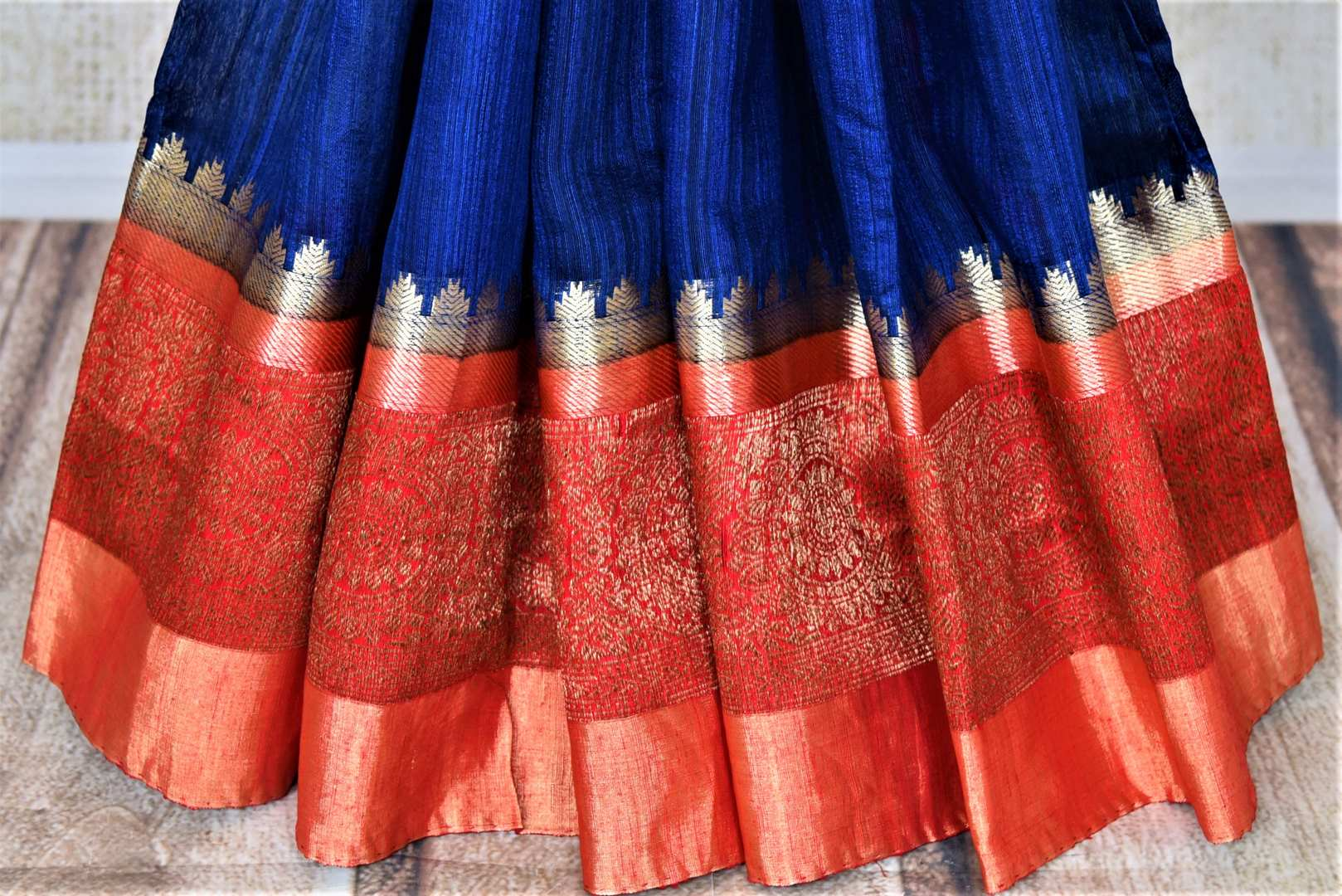 Shop ink blue tussar Banarsi saree online in USA with red zari border. Choose tasteful handloom sarees for special occasions from Pure Elegance. Our exclusive Indian fashion store has a myriad of exquisite pure silk saris, tussar sarees, Banarasi sarees for Indian women in USA.-pleats
