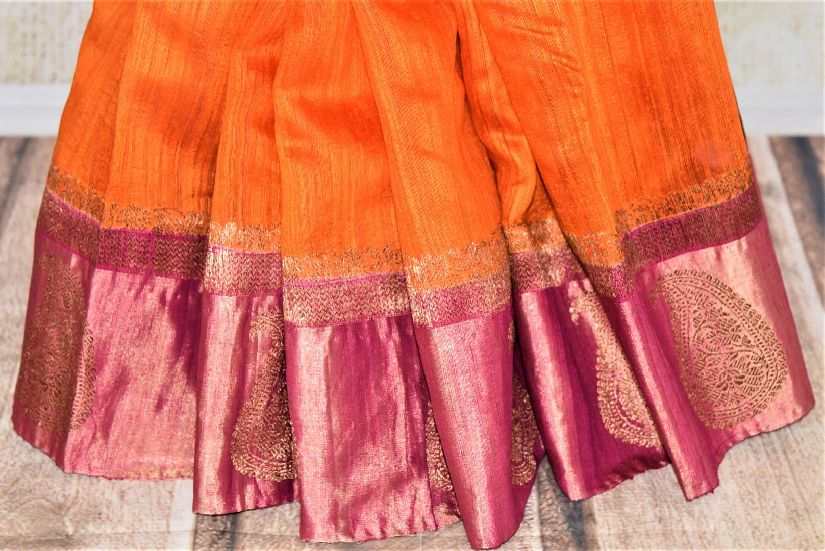 Shop stunning orange tussar Banarsi saree online in USA with zari work on pink border. Choose tasteful handloom sarees for special occasions from Pure Elegance. Our exclusive Indian fashion store has a myriad of exquisite pure silk saris, tussar sarees, Banarasi sarees for Indian women in USA.-pleats
