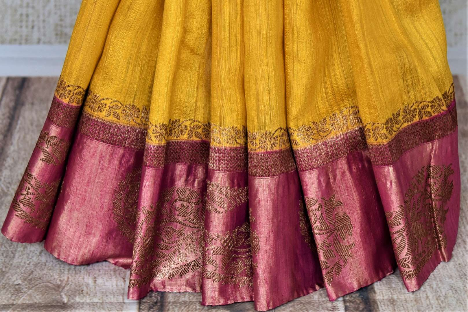 Buy bright yellow tussar Banarsi saree online in USA with zari work on pink border. Choose tasteful handloom sarees for special occasions from Pure Elegance. Our exclusive Indian fashion store has a myriad of exquisite pure silk saris, tussar sarees, Banarasi sarees for Indian women in USA.-pleats