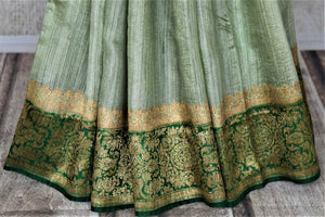 Shop mint green tussar Banarasi sari online in USA with green antique zari border. Keep your ethnic style updated with latest designer saris, handloom sarees, pure silk sarees from Pure Elegance Indian fashion store in USA.-pleats