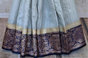 Shop elegant powder blue tussar Benarasi sari online in USA with dark blue antique zari border. Keep your ethnic style updated with latest designer saris, handloom sarees, pure silk sarees from Pure Elegance Indian fashion store in USA.-pleats