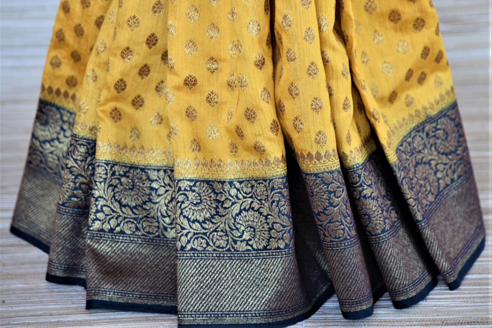 Buy stunning yellow muga Banarasi saree online in USA with blue antique zari border. Be an epitome of ethnic Indian fashion with traditional Banarasi sarees, georgette saris from Pure Elegance fashion store in USA.-pleats