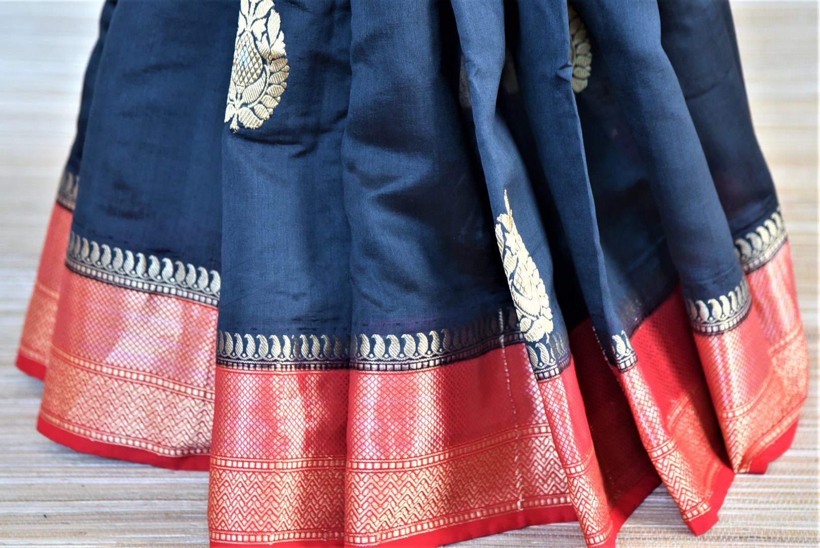 Shop gorgeous black Banarasi silk sari online in USA with red zari border and buta. Be a vision of tradition and elegance on weddings and festivals with exquisite Banarasi silk sarees, pure silk sarees, handwoven sarees from Pure Elegance Indian clothing store in USA.-pleats