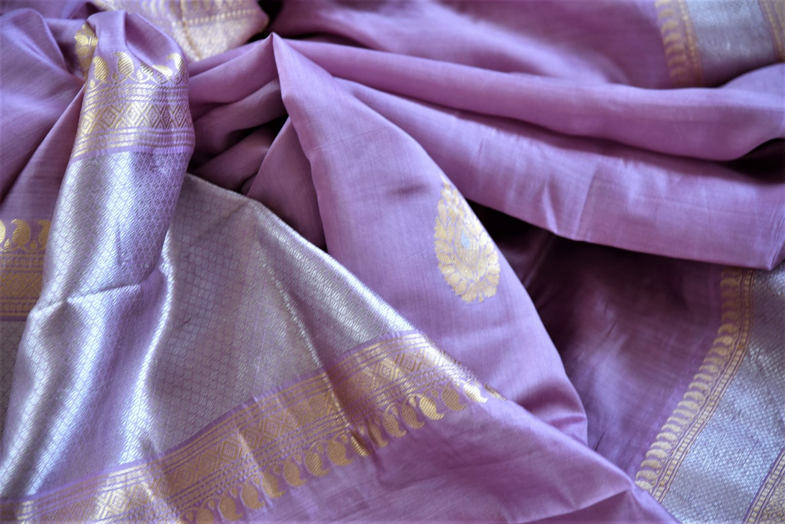 Buy lavender color Banarasi silk saree online in USA with silver golden zari border and buta. Be a vision of tradition and elegance on weddings and festivals with exquisite Banarasi silk sarees, pure silk sarees, handwoven sarees from Pure Elegance Indian clothing store in USA.-details