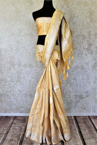 Buy attractive yellow tussar Banarasi sari online in USA with silver zari border and zari buta. Be the center of attraction at weddings and parties with beautiful silk sarees, tussar sarees, embroidered sarees, partywear sarees, fancy sarees from Pure Elegance Indian fashion store in USA. -full view