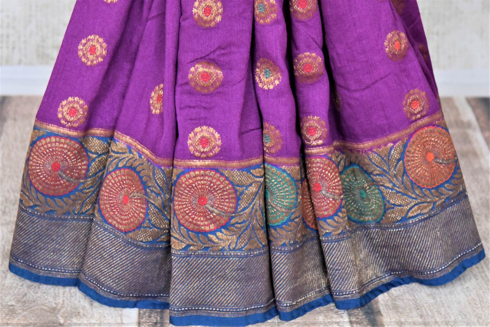 Shop gorgeous purple muga Banarasi saree online in USA with blue antique zari floral border. Keep your ethnic style updated with latest designer sarees, handloom sarees, pure silk sarees from Pure Elegance Indian fashion store in USA.-pleats