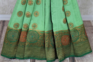 Buy pastel green muga Banarasi sari online in USA with dark green antique zari floral border. Keep your ethnic style updated with latest designer sarees, handloom sarees, pure silk sarees from Pure Elegance Indian fashion store in USA.-pleats