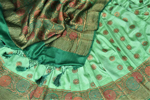 Buy pastel green muga Banarasi sari online in USA with dark green antique zari floral border. Keep your ethnic style updated with latest designer sarees, handloom sarees, pure silk sarees from Pure Elegance Indian fashion store in USA.-details