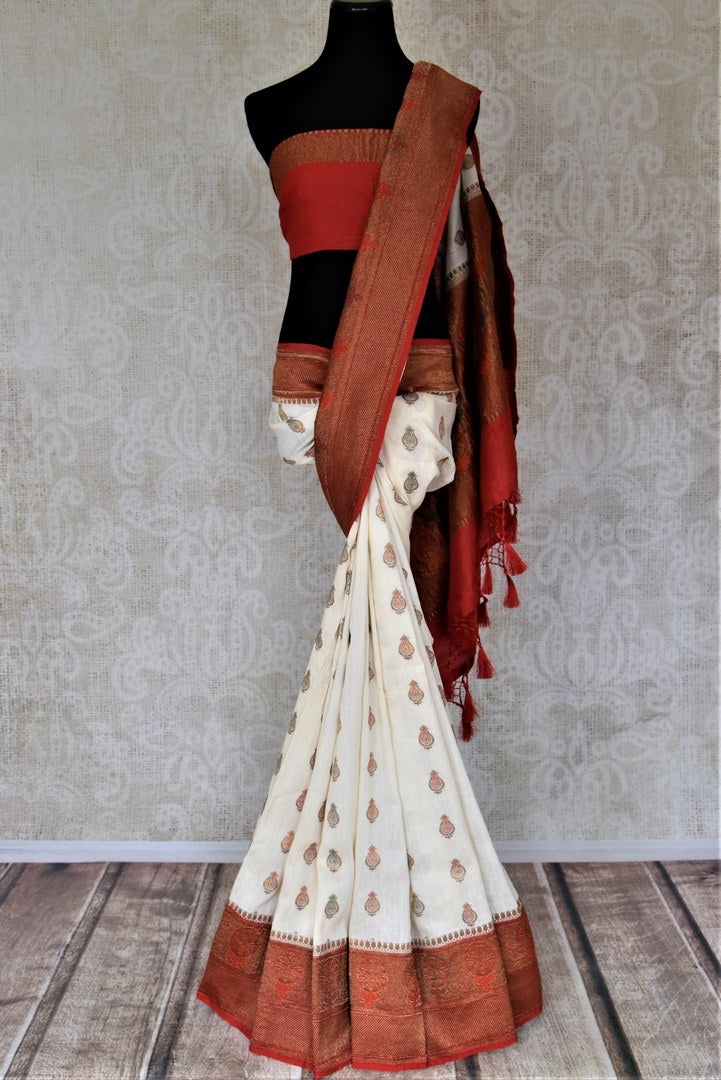 Buy lovely off-white muga Banarasi saree online in USA with red antique zari floral border. Keep your ethnic style updated with latest designer sarees, handloom sarees, pure silk sarees from Pure Elegance Indian fashion store in USA.-full view