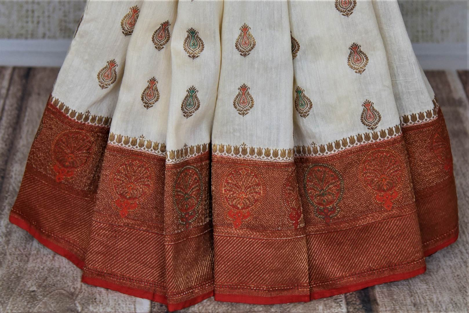 Buy lovely off-white muga Banarasi saree online in USA with red antique zari floral border. Keep your ethnic style updated with latest designer sarees, handloom sarees, pure silk sarees from Pure Elegance Indian fashion store in USA.-pleats