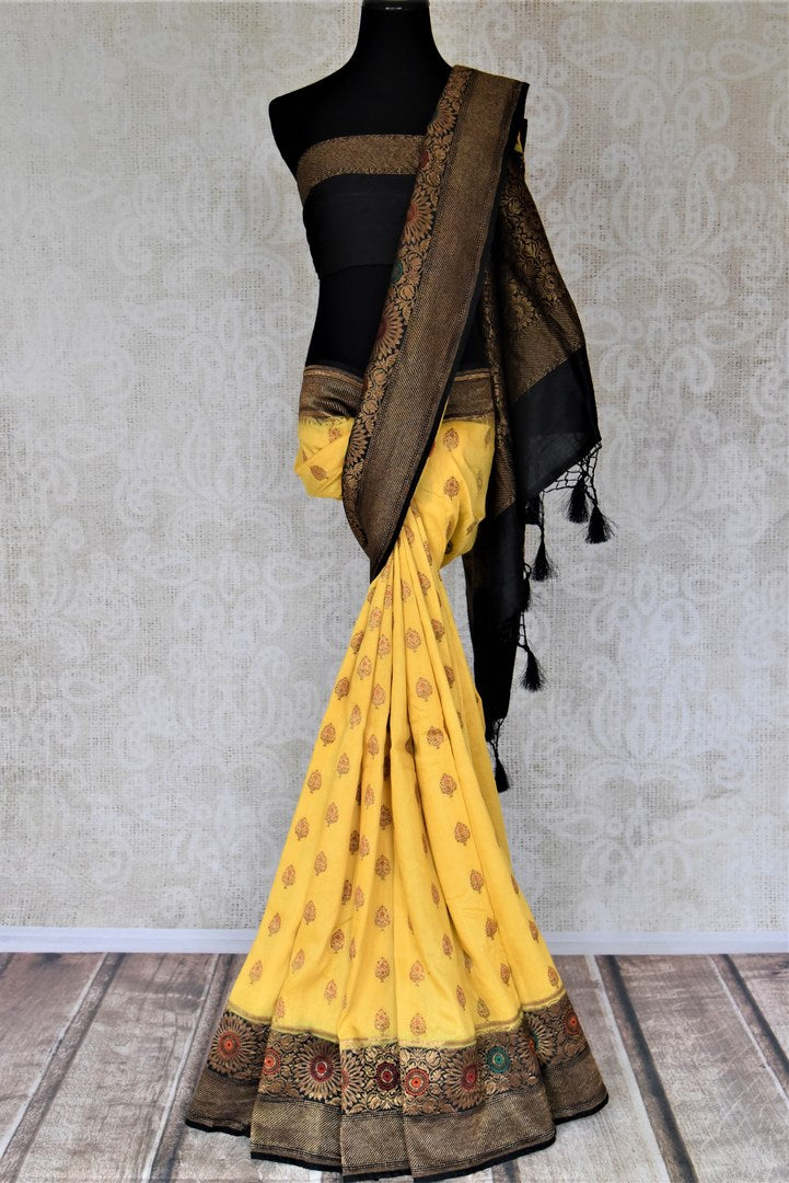 Shop stunning yellow muga Banarasi sari online in USA with black antique zari floral border. Keep your ethnic style updated with latest designer sarees, handloom sarees, pure silk sarees from Pure Elegance Indian fashion store in USA.-full view