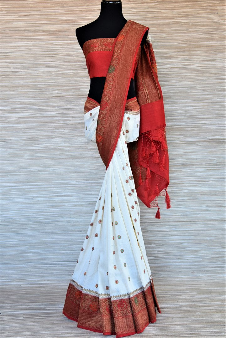 Shop traditional off-white muga Banarasi saree online in USA with antique zari minakari red border and buta. Be a vision of tradition and elegance on weddings and festivals with exquisite Banarasi silk sarees, pure silk sarees, handwoven sarees from Pure Elegance Indian clothing store in USA.-full view