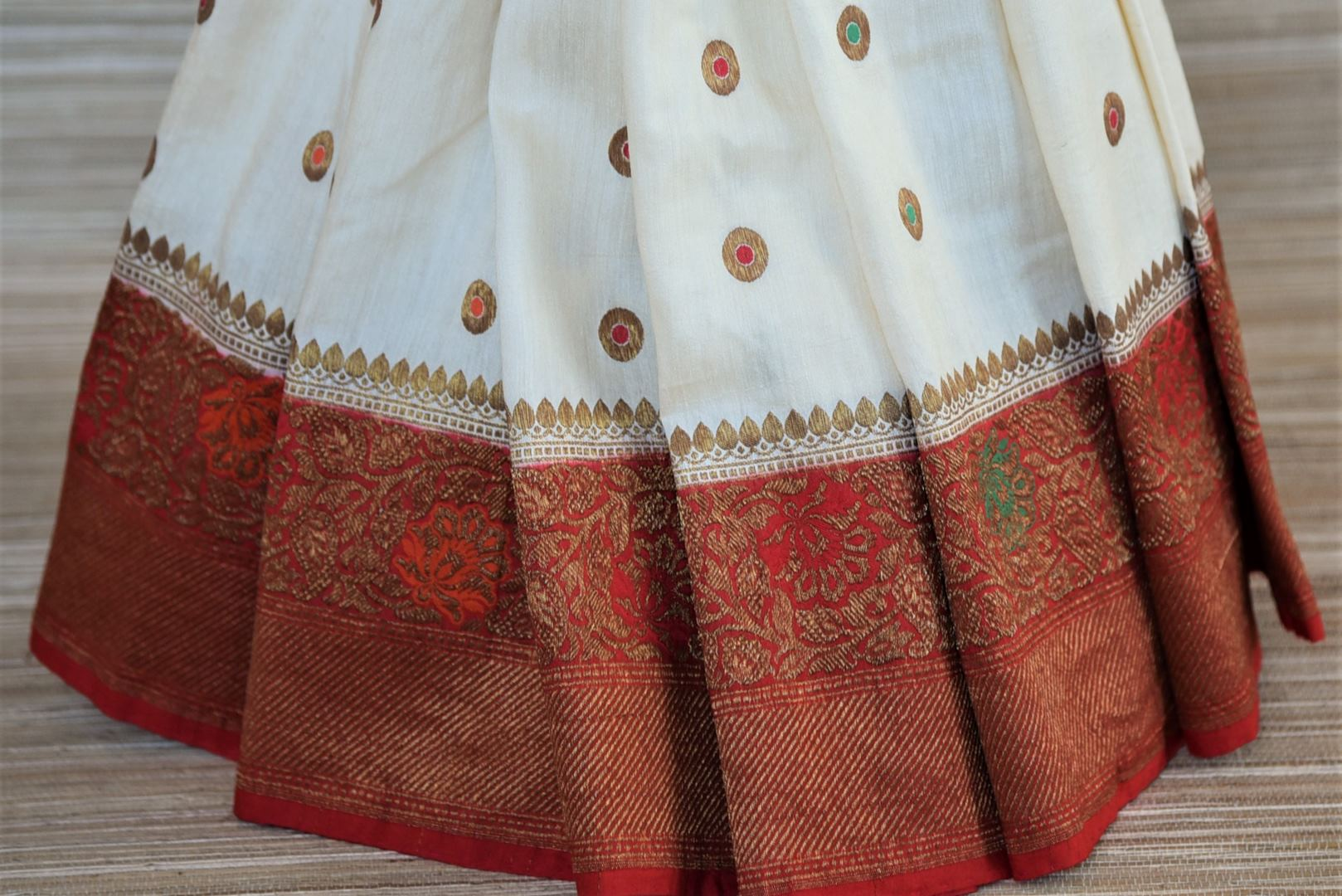Shop traditional off-white muga Banarasi saree online in USA with antique zari minakari red border and buta. Be a vision of tradition and elegance on weddings and festivals with exquisite Banarasi silk sarees, pure silk sarees, handwoven sarees from Pure Elegance Indian clothing store in USA.-pleats