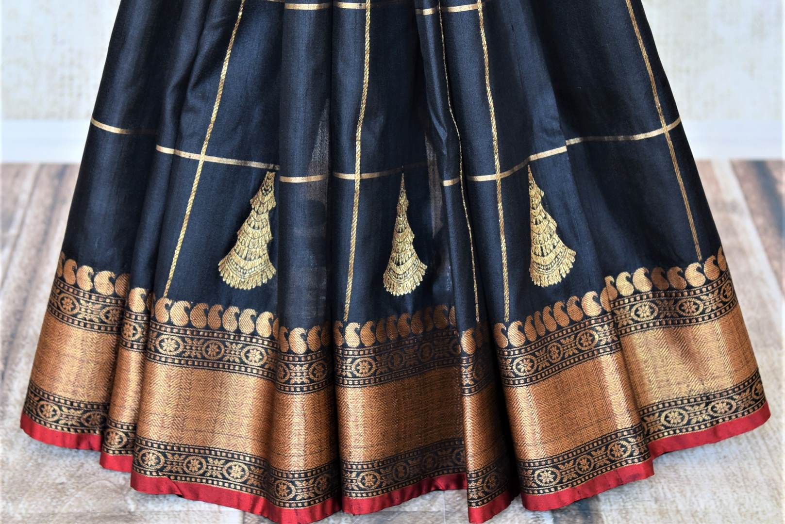 Shop stunning black tassar Banarasi saree online in USA with zari checks and antique zari border. For Indian women in USA, Pure Elegance Indian fashion store brings an exquisite collection Banarasi sarees, Banarasi silk saris, tussar sarees,  work sarees, pure silk sarees all under one roof. Shop online now.-pleats