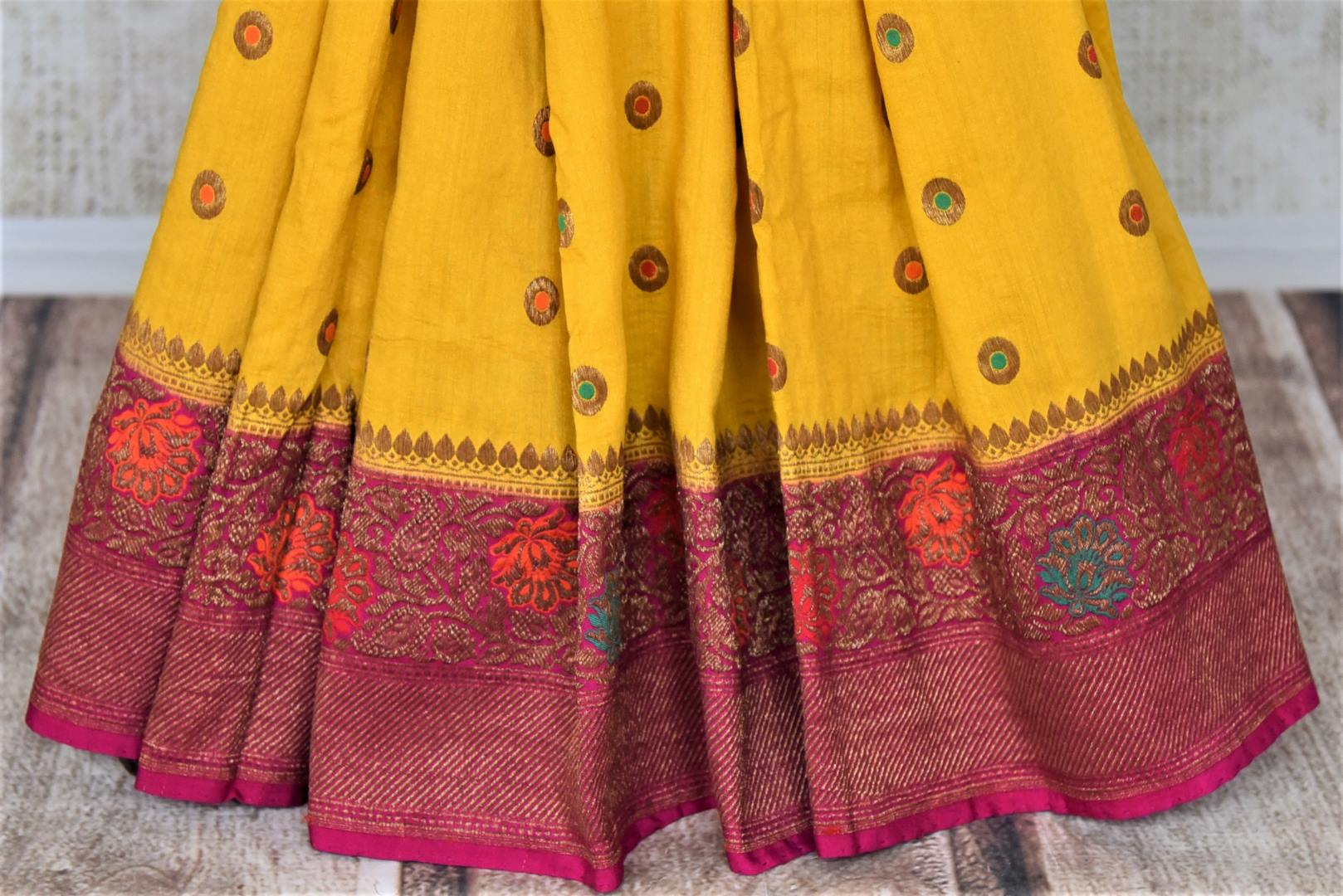 Buy yellow muga Benarasi saree online in USA with pink antique zari floral border. Keep your ethnic style updated with latest designer sarees, handloom sarees, muga silk sarees from Pure Elegance Indian fashion store in USA.-pleats
