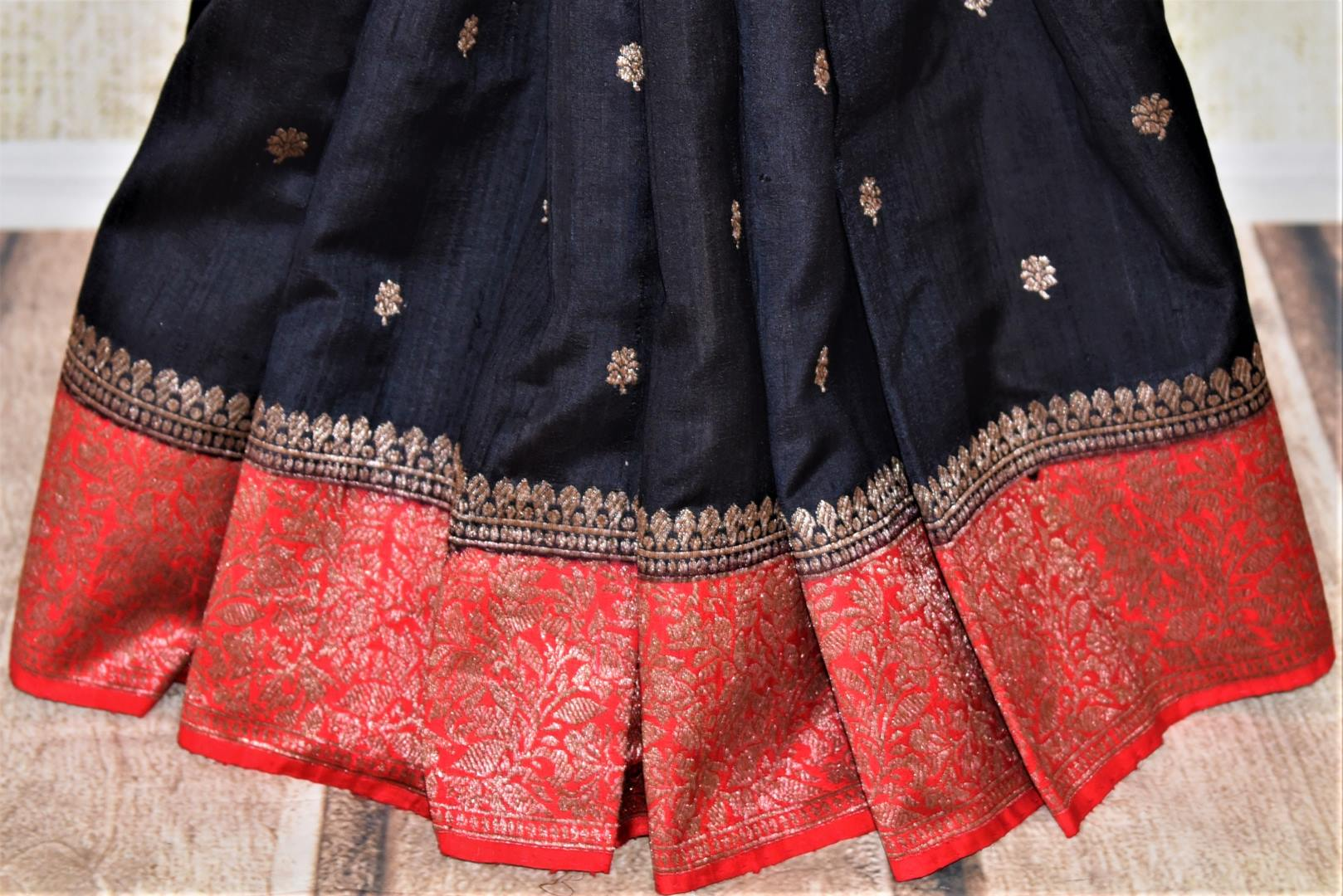 Buy black tussar Banarasi sari online in USA with zari buta and red zari border. Choose tasteful handloom saris for special occasions from Pure Elegance. Our exclusive Indian fashion store has a myriad of exquisite pure silk saris, tussar sarees, Banarasi sarees for Indian women in USA.-pleats