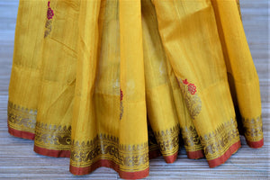 Shop beautiful yellow tassar Benarasi saree online in USA with antique zari floral border. Wear designer sarees, Banarasi sarees, handwoven tussar sarees on special occasions from Pure Elegance Indian clothing store in USA. -pleats