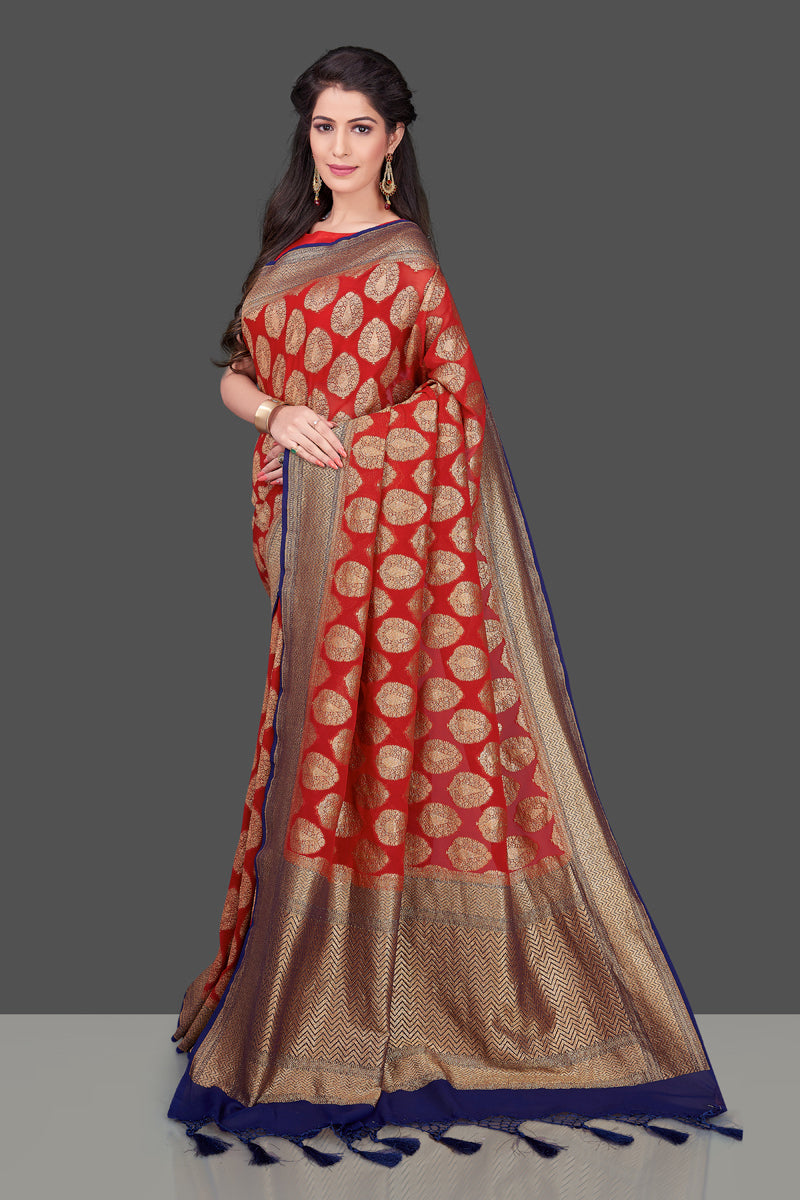 Buy bright red georgette Banarasi sari online in USA with blue zari border. Shop beautiful Banarasi sarees, georgette sarees, pure muga silk sarees in USA from Pure Elegance Indian fashion boutique in USA. Get spoiled for choices with a splendid variety of Indian saris to choose from! Shop now.-full view
