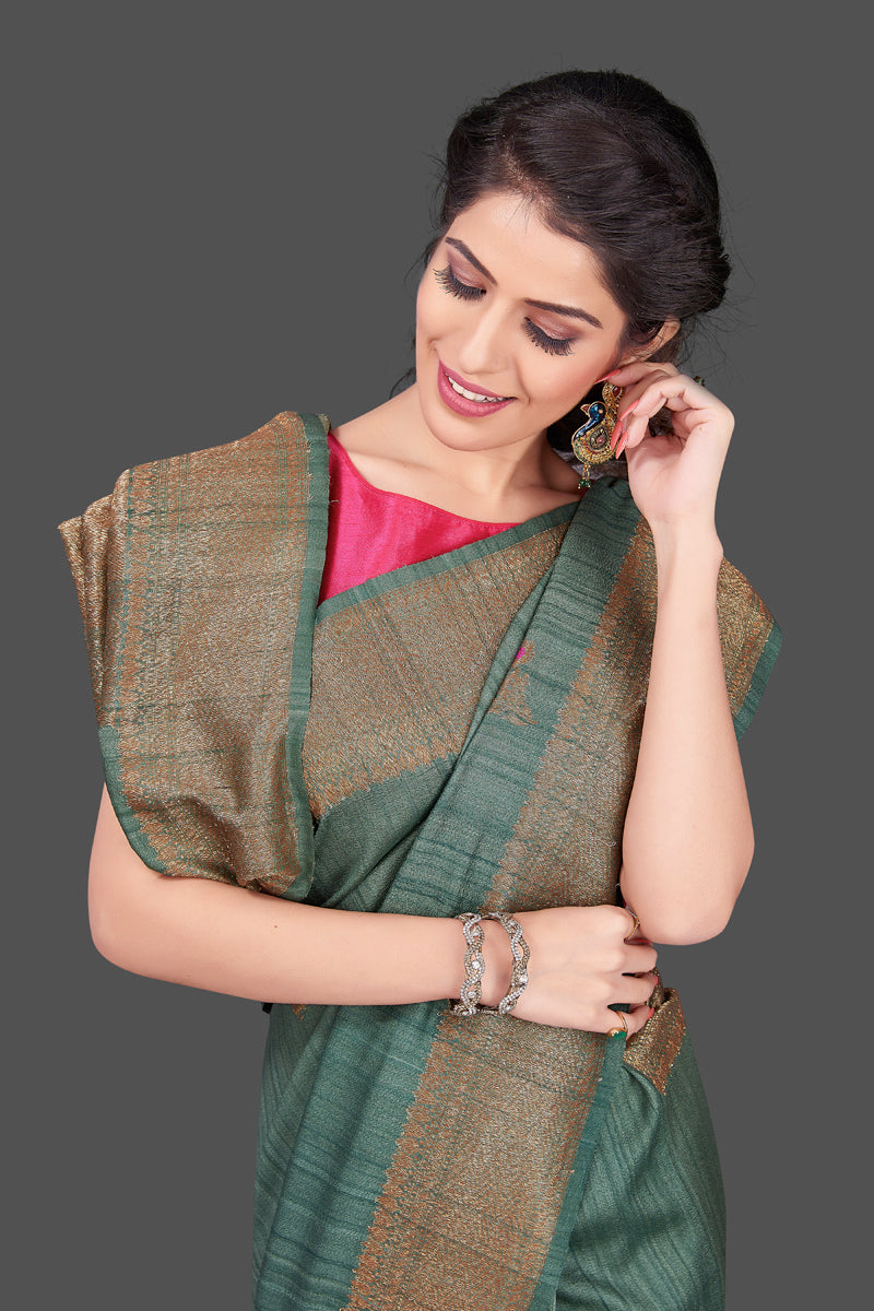 Shop elegant green tussar Banarasi sari online in USA with antique zari minakari buta. Shop beautiful Banarasi sarees, tussar sarees, pure muga silk sarees in USA from Pure Elegance Indian fashion boutique in USA. Get spoiled for choices with a splendid variety of Indian saris to choose from! Shop now.-closeup