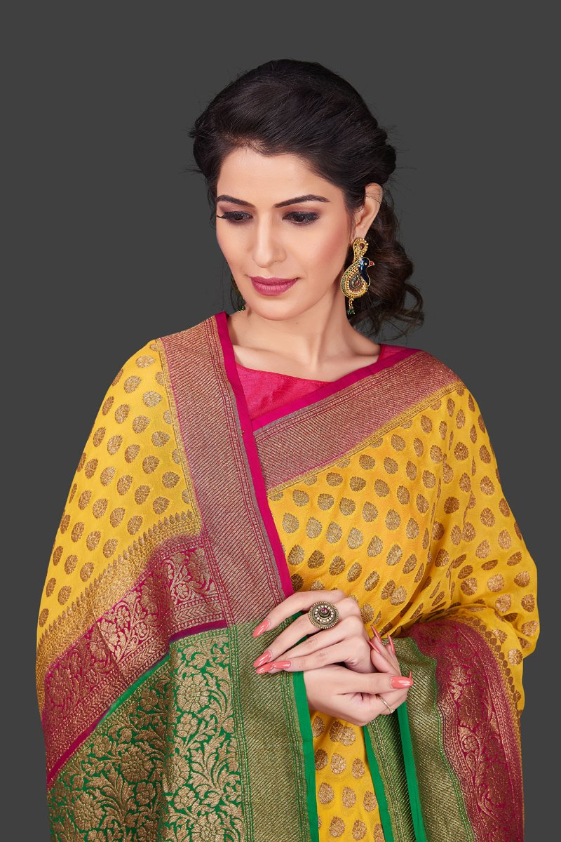 Shop online yellow georgette Benarasi saree in USA with pink green zari border. Shop beautiful Banarasi georgette sarees, tussar saris, pure muga silk saris in USA from Pure Elegance Indian fashion boutique in USA. Get spoiled for choices with a splendid variety of Indian sarees to choose from! Shop now.-closeup
