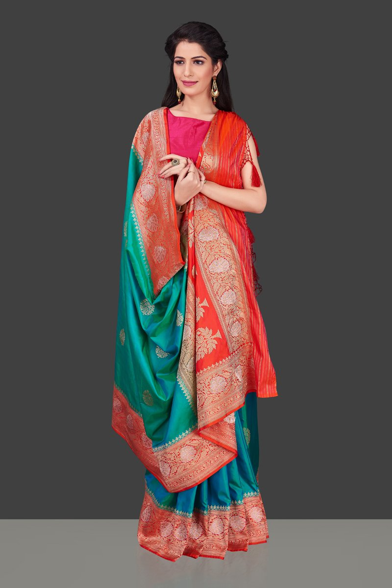 Shop blue green Benarasi silk saree online in USA with red zari border. Shop beautiful Banarasi georgette sarees, tussar saris, pure muga silk saris in USA from Pure Elegance Indian fashion boutique in USA. Get spoiled for choices with a splendid variety of Indian sarees to choose from! Shop now.-front