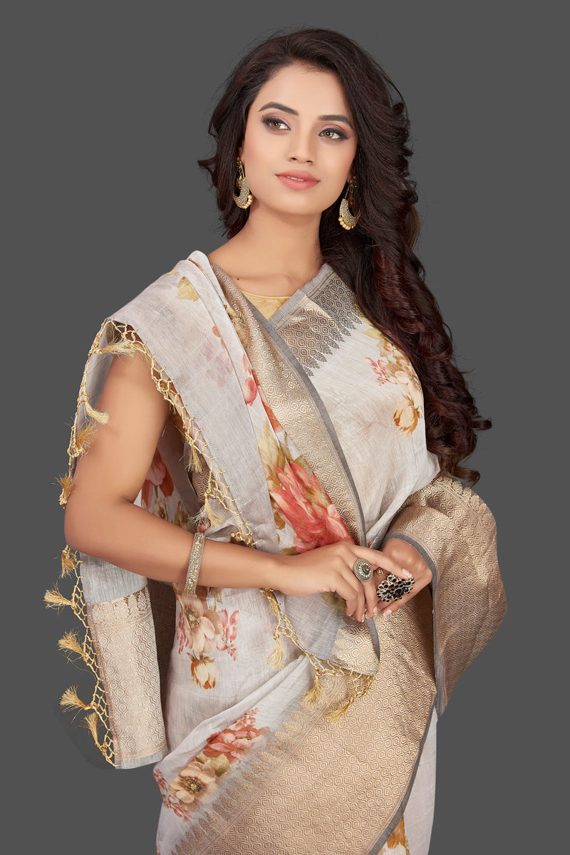 Shop gorgeous light grey floral Banarasi linen sari online in USA with golden zari border. Look charming on festivals and weddings with stunning Banarasi sarees from Pure Elegance Indian clothing store. Your one stop destination for Indian fashion in USA!-closeup