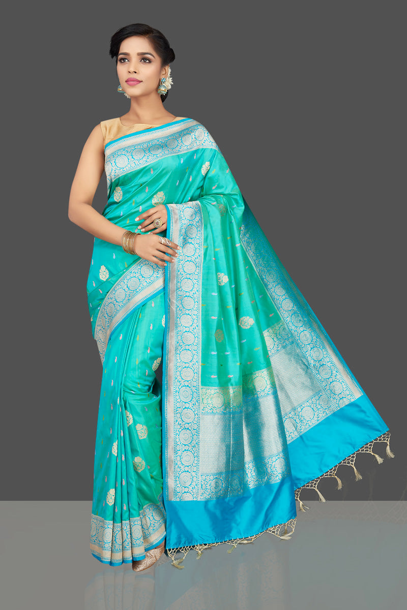 Shop lovely greenish blue Banarasi silk saree online in USA with silver zari buta. Be the center of attraction at weddings and parties with your captivating ethnic style in beautiful Banarasi silk sarees. zari work saris from Pure Elegance Indian fashion store in USA.-full view