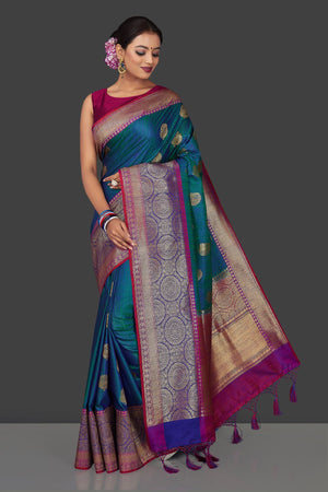 Buy stunning greenish blue tassar Banarasi sari online in USA with antique zari purple and blue border and zari buta. Garner compliments on weddings and special occasions with exquisite Banarasi saris, handwoven silk sarees, tussar sarees from Pure Elegance Indian fashion store in USA.-front