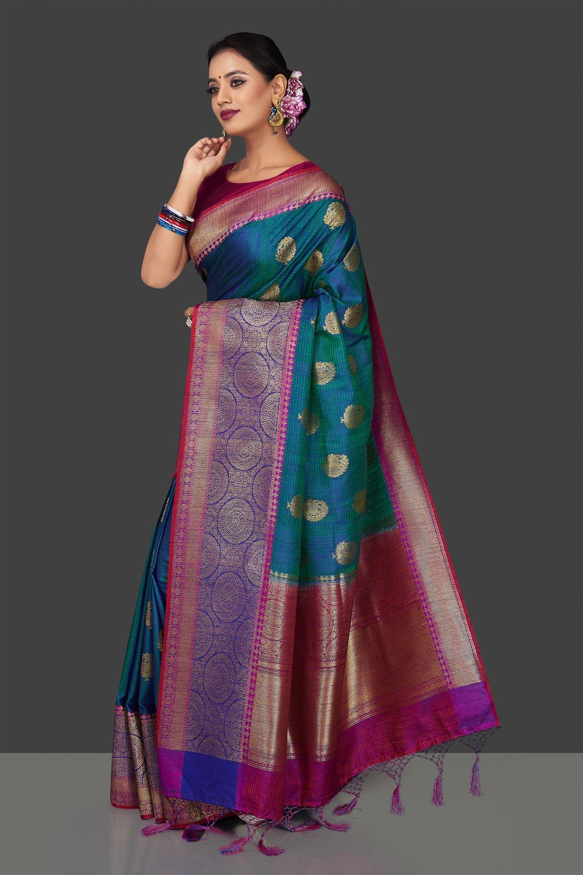 Buy stunning greenish blue tassar Banarasi sari online in USA with antique zari purple and blue border and zari buta. Garner compliments on weddings and special occasions with exquisite Banarasi saris, handwoven silk sarees, tussar sarees from Pure Elegance Indian fashion store in USA.-full view
