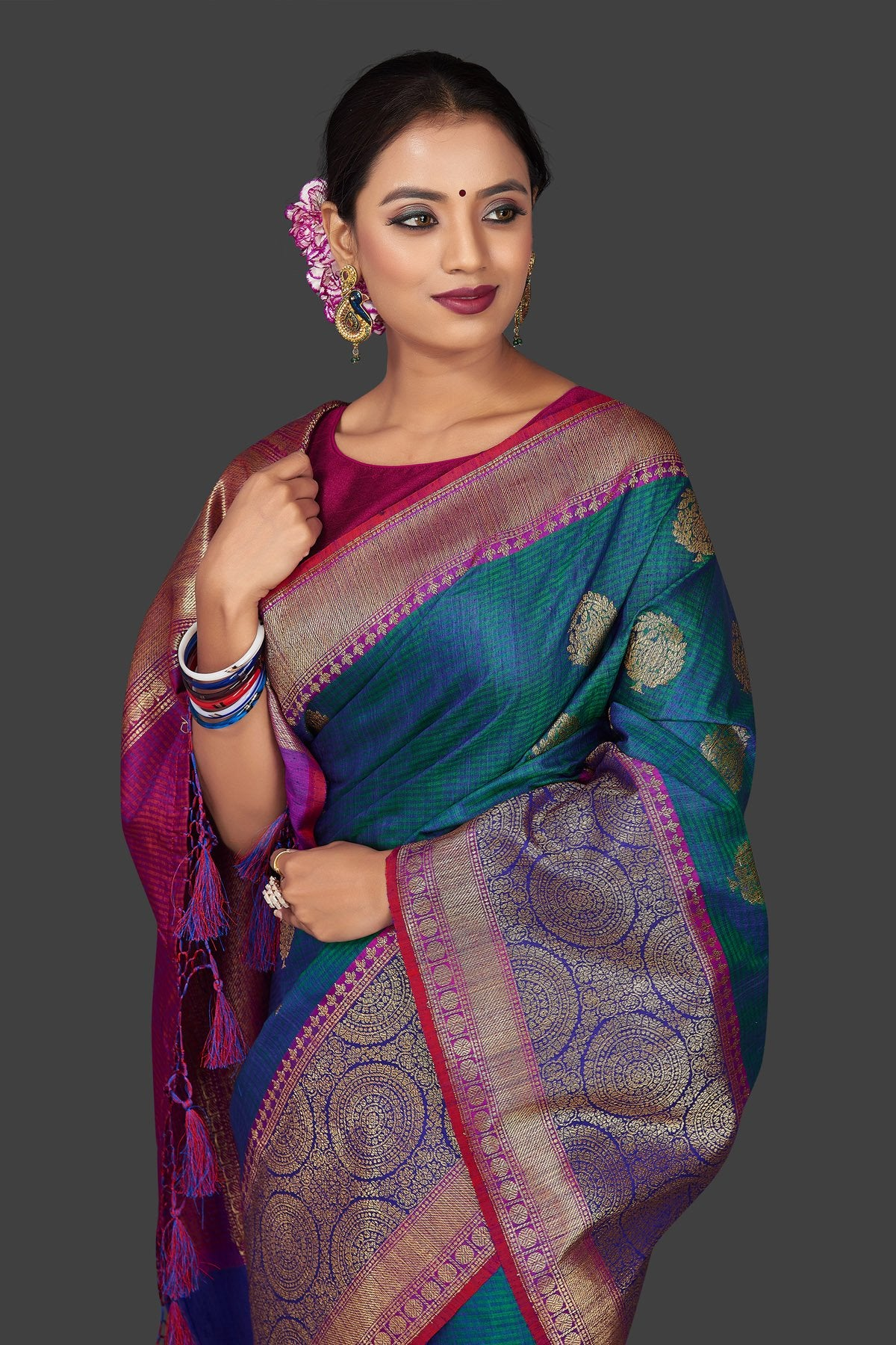 Buy stunning greenish blue tassar Banarasi sari online in USA with antique zari purple and blue border and zari buta. Garner compliments on weddings and special occasions with exquisite Banarasi saris, handwoven silk sarees, tussar sarees from Pure Elegance Indian fashion store in USA.-closeup