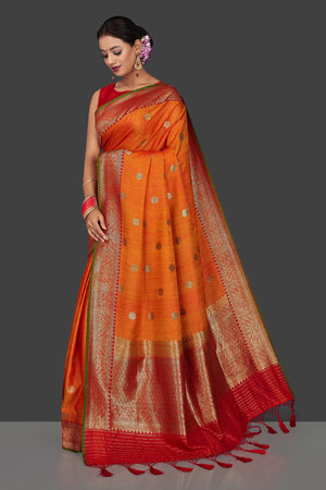 Shop beautiful orange tassar Banarasi saree online in USA with antique zari red border and zari buta. Garner compliments on weddings and special occasions with exquisite Banarasi saris, handwoven silk sarees, tussar sarees from Pure Elegance Indian fashion store in USA.-pallu