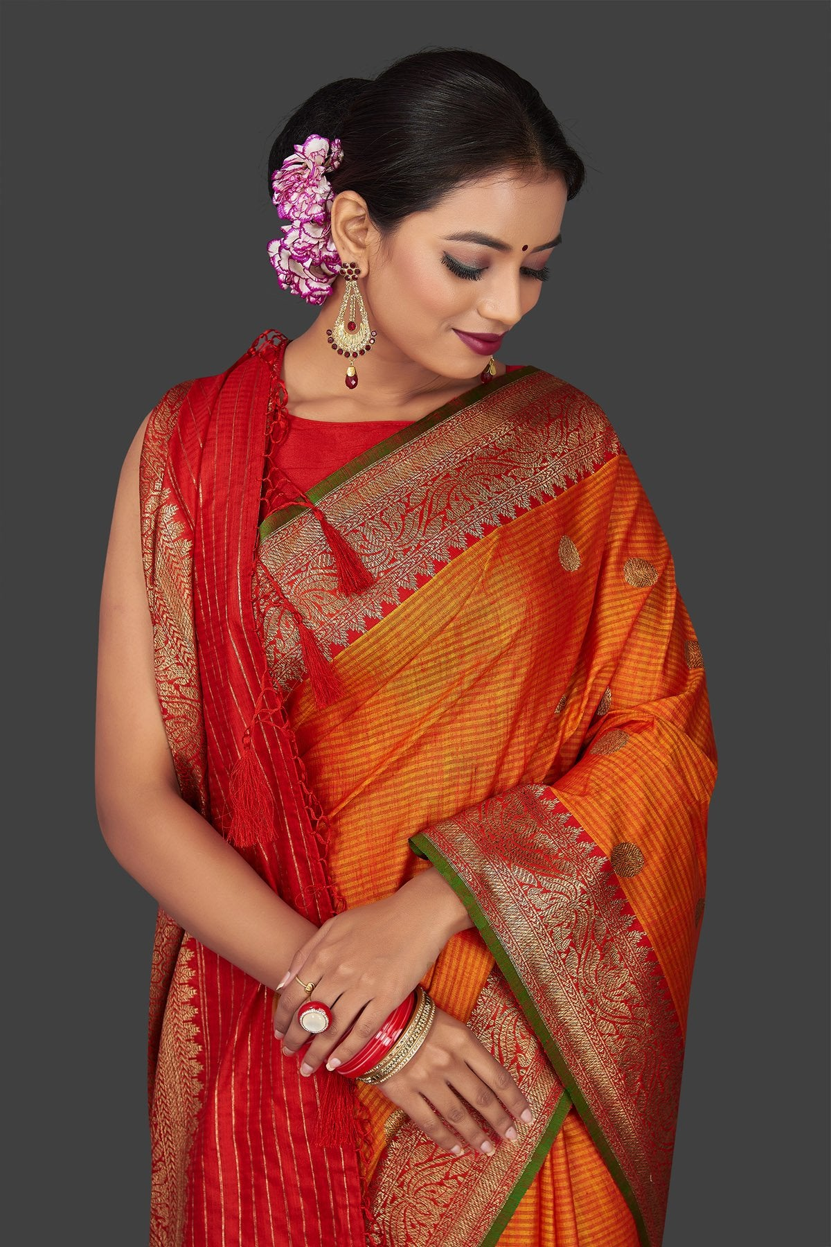 Shop beautiful orange tassar Banarasi saree online in USA with antique zari red border and zari buta. Garner compliments on weddings and special occasions with exquisite Banarasi saris, handwoven silk sarees, tussar sarees from Pure Elegance Indian fashion store in USA.-closeup