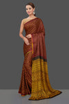 Buy beautiful dark brown gajji silk Bandhani saree online in USA with yellow Ajrakh pallu. Stand out at weddings and festive occasions with your tasteful choice in this gorgeous pure silk saris,  printed sarees, Bandhej saris, handwoven sarees from Pure Elegance Indian fashion store in USA. -full view