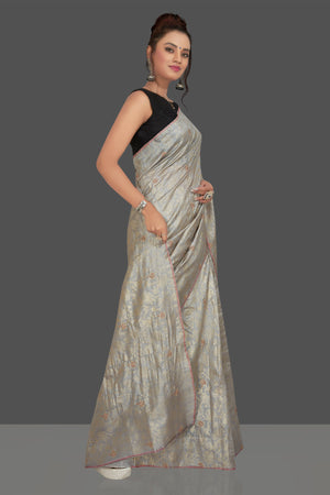 Buy gorgeous light grey embroidered tussar sari online in USA with floral zari work. Shop beautiful tussar sarees, hand embroidered saris, georgette sarees, designer sarees in USA from Pure Elegance Indian fashion store in USA. Shop online now.-side