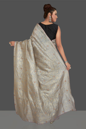 Buy gorgeous light grey embroidered tussar sari online in USA with floral zari work. Shop beautiful tussar sarees, hand embroidered saris, georgette sarees, designer sarees in USA from Pure Elegance Indian fashion store in USA. Shop online now.-back
