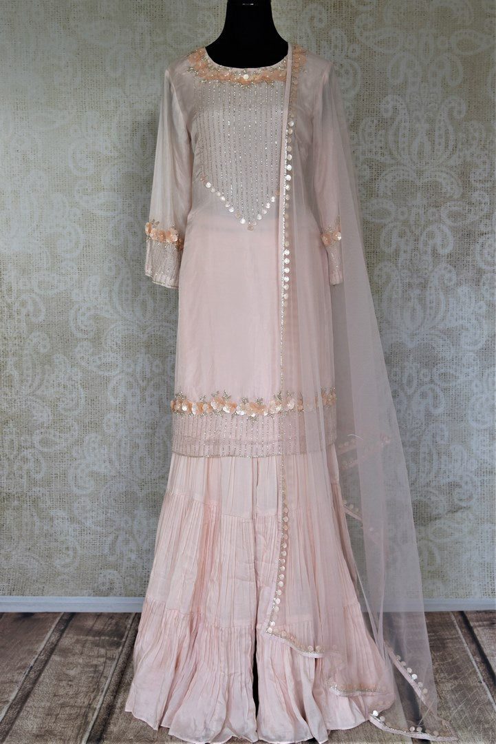 Shop gorgeous powder pink hand embroidered silk sharara suit online in USA with matching dupatta. Elevate your ethnic style on weddings and festive occasions with stunning designer Anarkali suits, sharara suits, palazzo suits, salwar suits from Pure Elegance Indian fashion boutique in USA.-full view