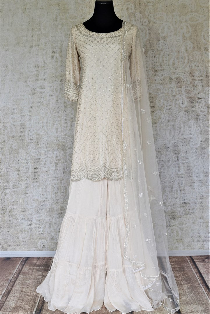 Shop beautifull cream hand embroidered silk sharara suit online in USA with dupatta. Elevate your ethnic style on weddings and festive occasions with stunning designer Anarkali suits, sharara suits, palazzo suits, salwar suits from Pure Elegance Indian fashion boutique in USA.-full view