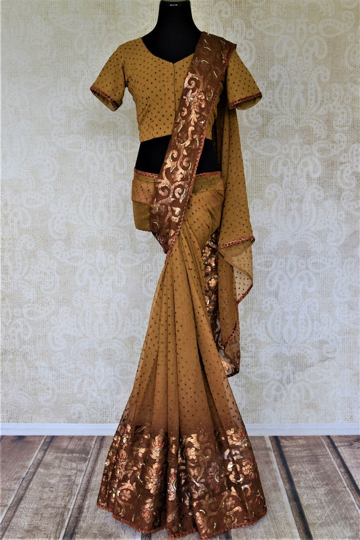 Buy beautiful brown chiffon saree online in USA with golden floral border and saree blouse. Keep it elegant on special occasions and parties with stunning designer sarees, embroidered sarees, fancy sarees, Bollywood sarees from Pure Elegance Indian fashion store in USA.-full view