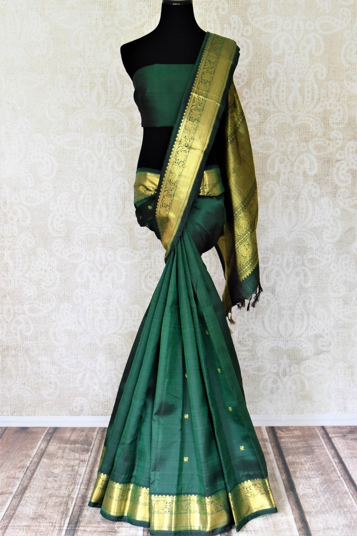 Buy beautiful dark green Kanjivaram saree online in USA with zari buta and golden zari border. Shop exquisite Indian sarees, Kanchipuram silk sarees, pure zari work sarees in USA from Pure Elegance Indian saree store in USA.-full view